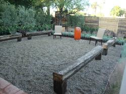 Gravel Patio with Focal Fountian and Used Railroad Tie Benches & Garden By Design